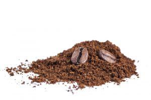 Coffee beans and coffee grounds on white background.