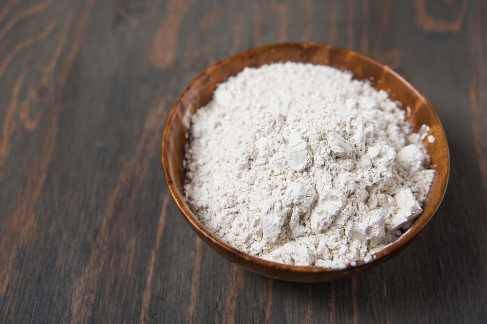 Diatomaceous Earth in wooden bowl on wooden background.