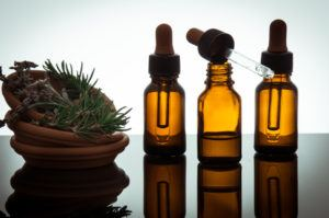 Essential oil with rosemary and lavender flowers.