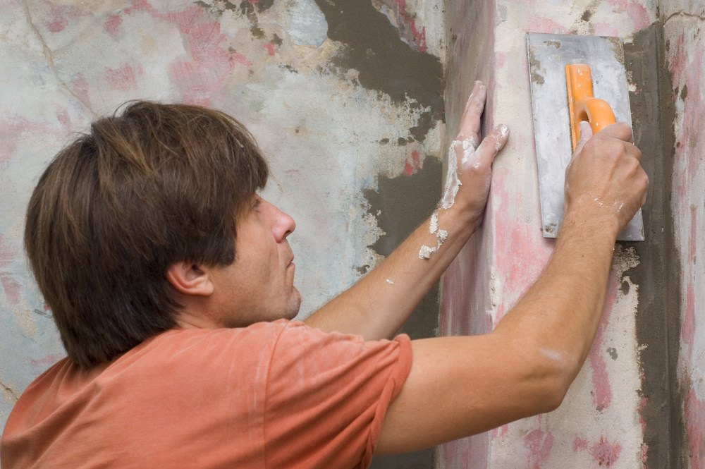 A man in orange shirt is plastering for the caulk cracks and crevices.