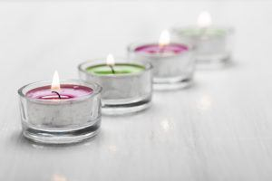 Four Burning Tea Lights on a white wooden surface.