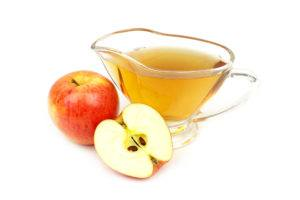 Close up of a cup of vinegar with one and a half apples beside.