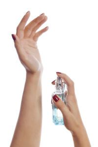 A woman is using oil spray on her hand in the air.