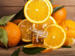 Bottle of essential oil from oranges on wooden background.
