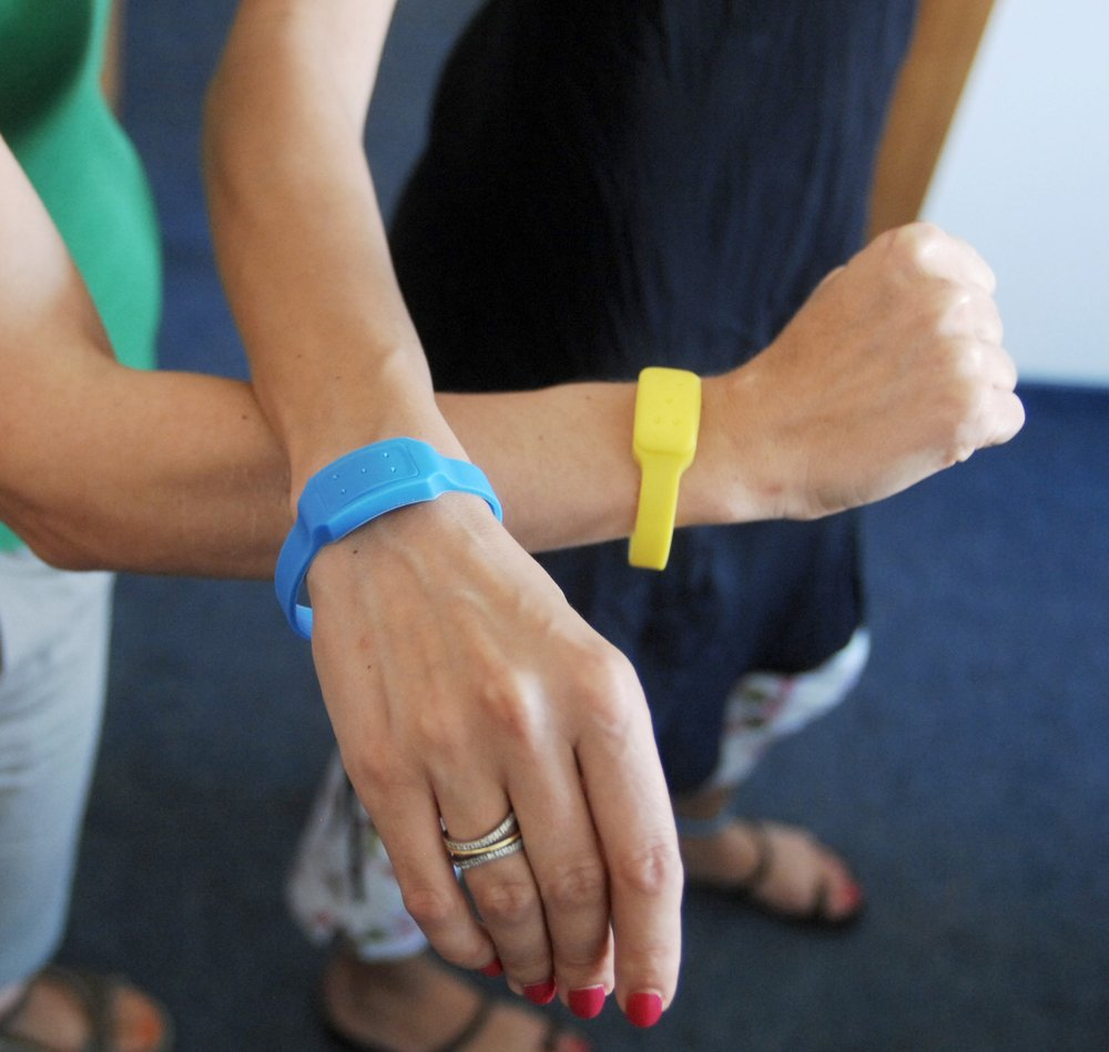 A pair of Anti-insect bracelet on humans' hands.
