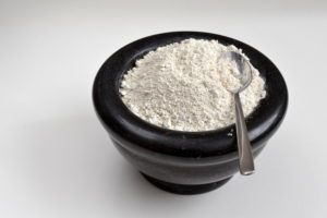 Bowl of diatomaceous earth with spoon.