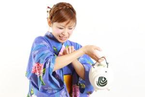 Young woman wearing Japanese kimono with mosquito coil, bitten by mosquito.
