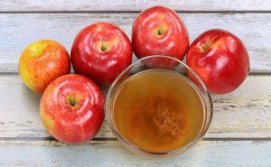 Apple cider vinegar with five apples on wooden table