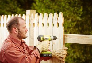 Man building a fence in garden