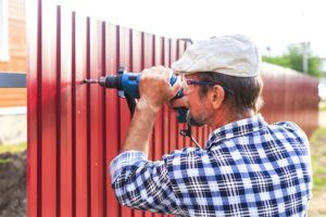An elderly man with a drill builds metal fence