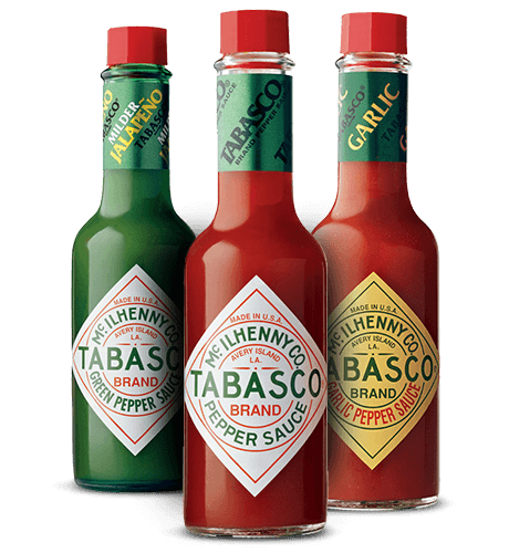 Three bottles of tabasco on the white.