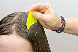 Brushing hair to treat head lice