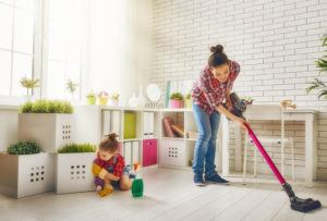 A young woman and a little child girl are wiping the dust and vacuumed the floor.