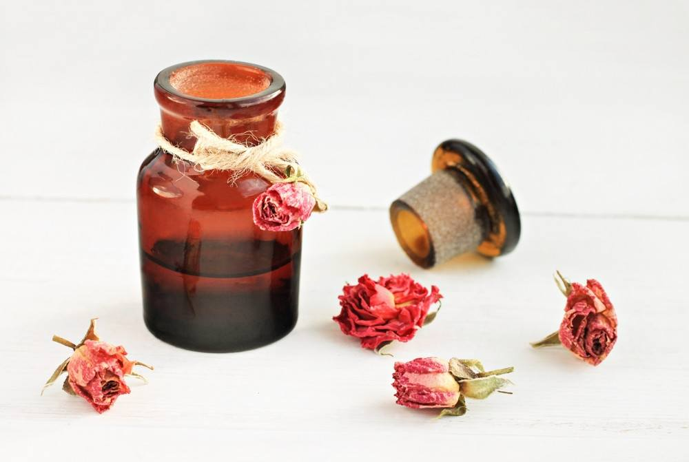 Apothecary dark glass bottle of essential oil, dried rosebuds on white table.