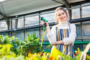 Smiling woman standing in orangery and holding garden hose