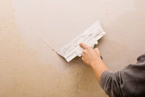 Man sealing the little cracks in wall
