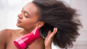 A girl is blowing dry hair.