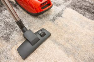 Vacuum cleaner being used while vacuuming a carpet