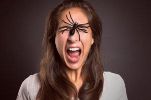 Woman with spider on her face.