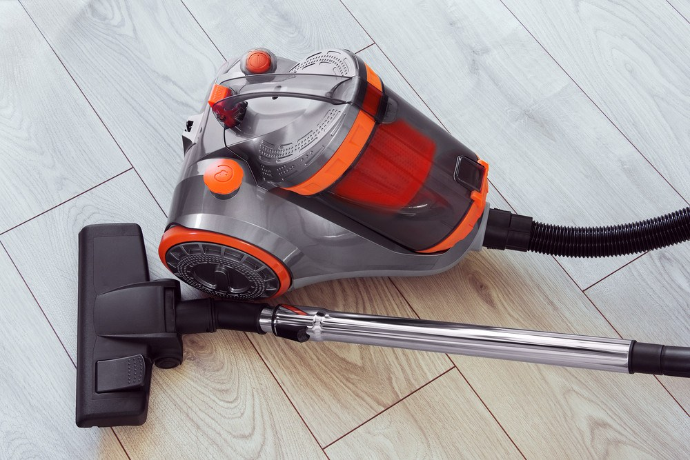 Vacuum cleaner with orange color on gray laminate.