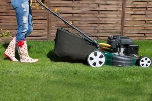 Woman mowing with lawn mower in the garden.