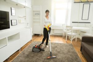 Young smiling woman vacuum cleaning the carpet in the living room.