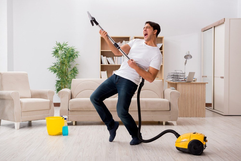 Man cleaning home with vacuum cleaner.